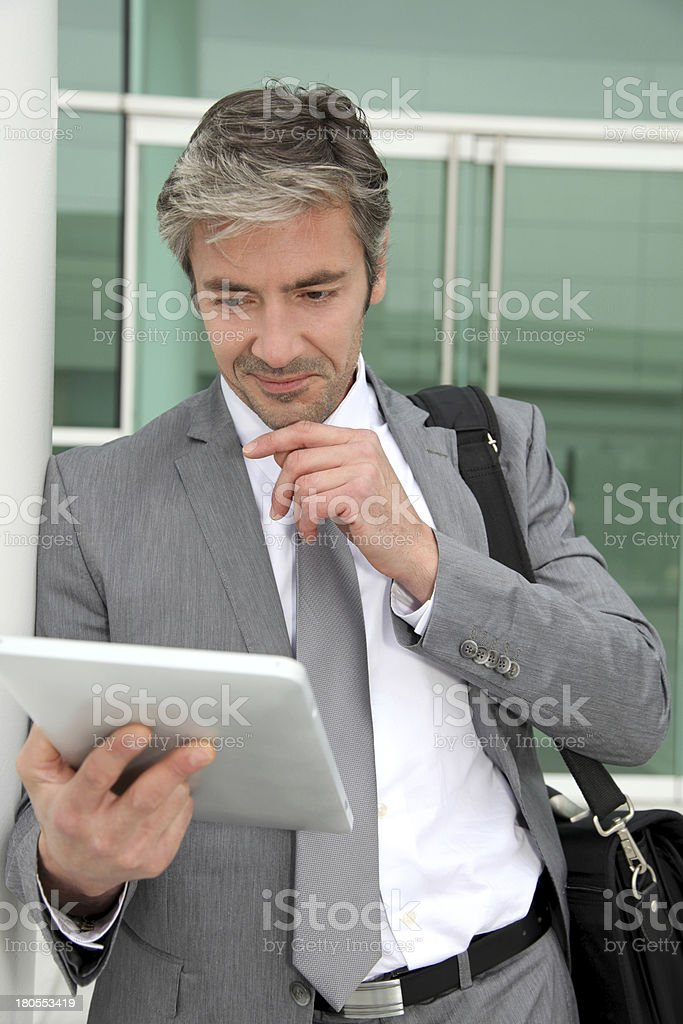 Smiling businessman leaning on wall in front of building royalty-free stock photo