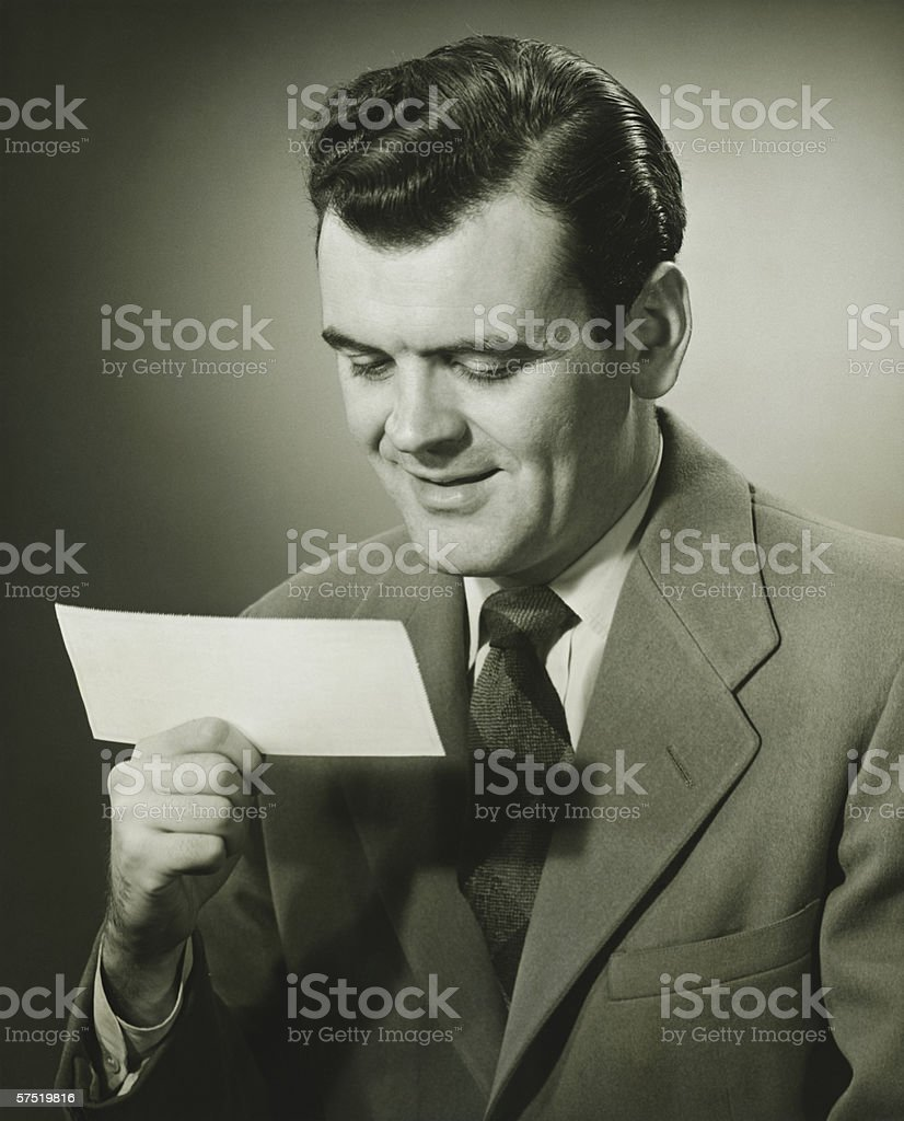 Smiling businessman looking at bank check, (B&W), portrait royalty-free stock photo