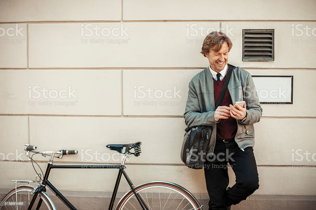 Smiling businessman looking at mobile phone stock photo