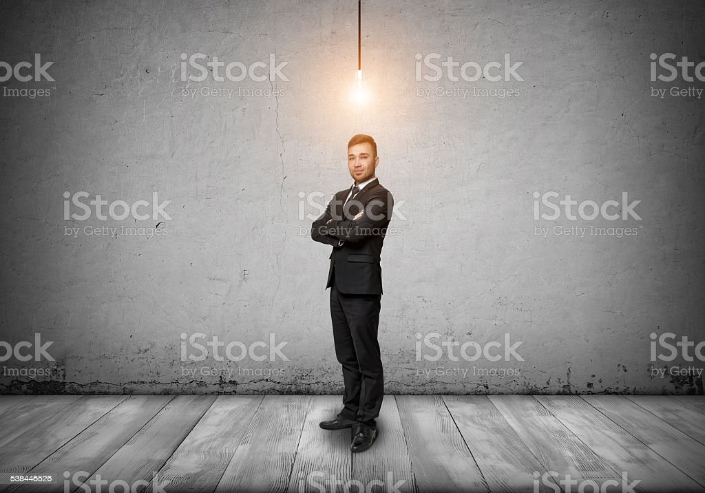 Smiling businessman looking at the camera with glowing bulb over stock photo