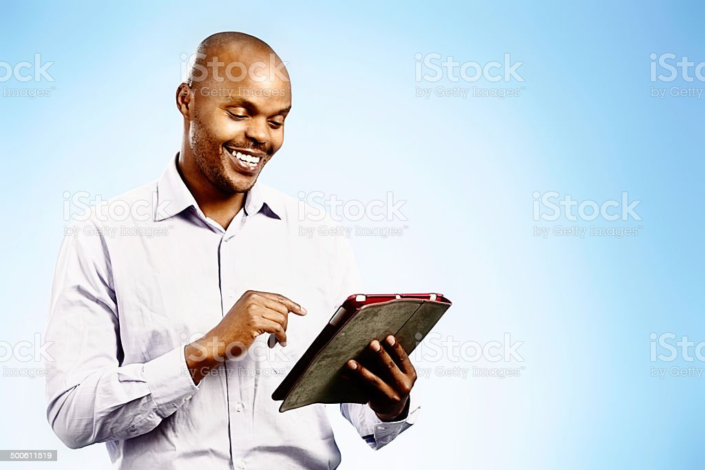 Smiling businessman looking down at his digital tablet stock photo