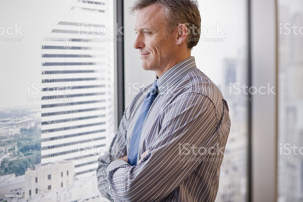 Smiling businessman looking out office window stock photo