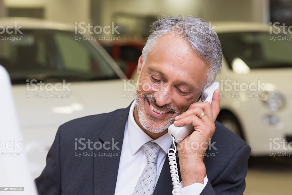 Smiling businessman making a phone call stock photo