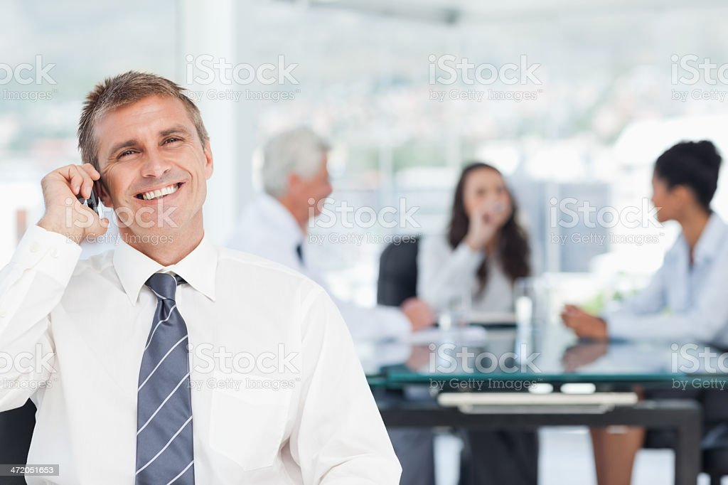 Smiling businessman on his cellphone with meeting behind him stock photo
