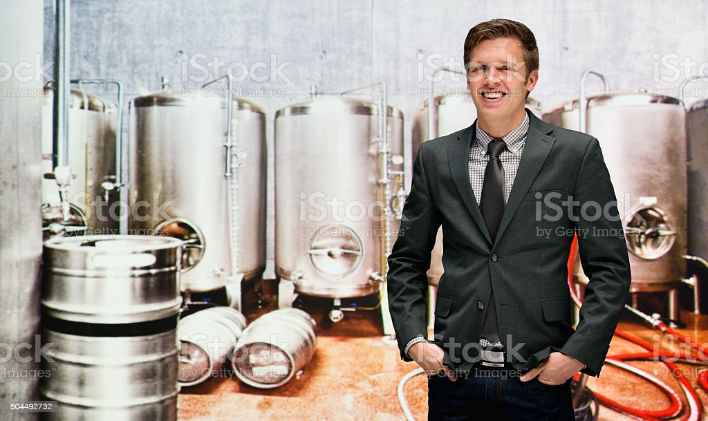 Smiling businessman on mobile at a brewery stock photo