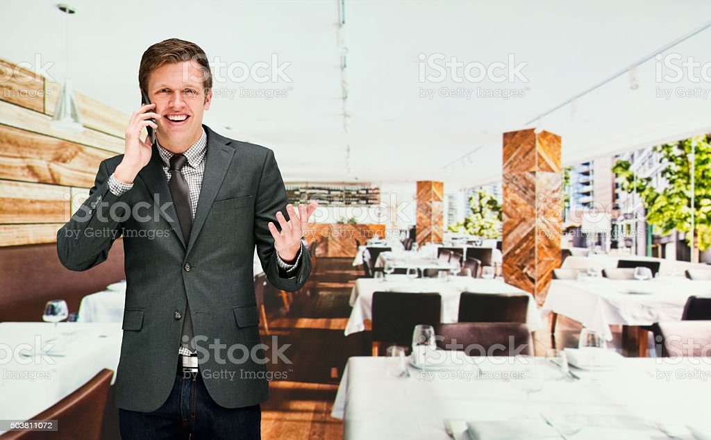 Smiling businessman on mobile in restaurant stock photo
