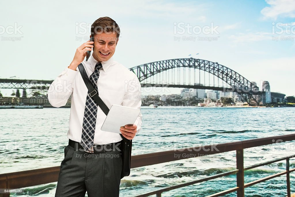 Smiling businessman on phone and using tablet stock photo