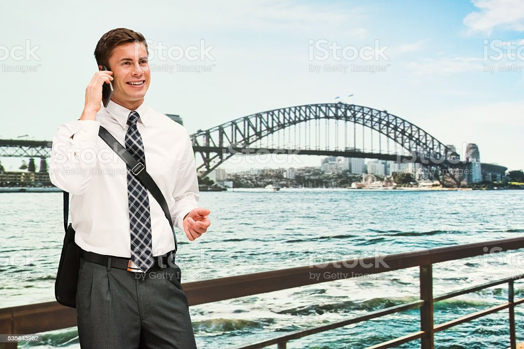Smiling businessman on phone outdoors stock photo