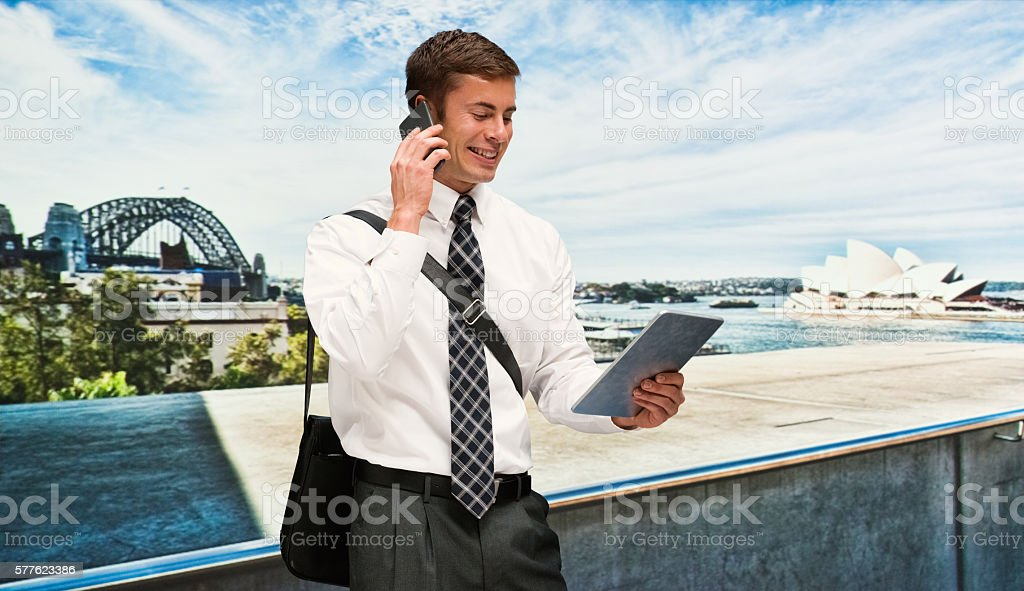Smiling businessman on phone while using tablet stock photo