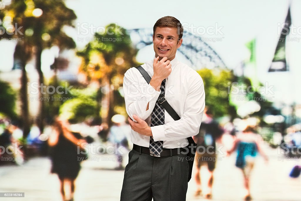 Smiling businessman outdoors and thinking stock photo