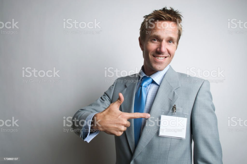 Smiling Businessman Pointing at Name Tag royalty-free stock photo