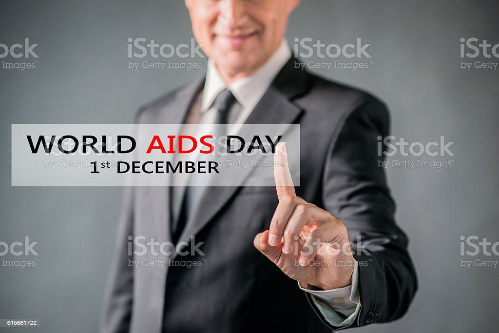Smiling businessman pointing at world aids day virtual sign stock photo