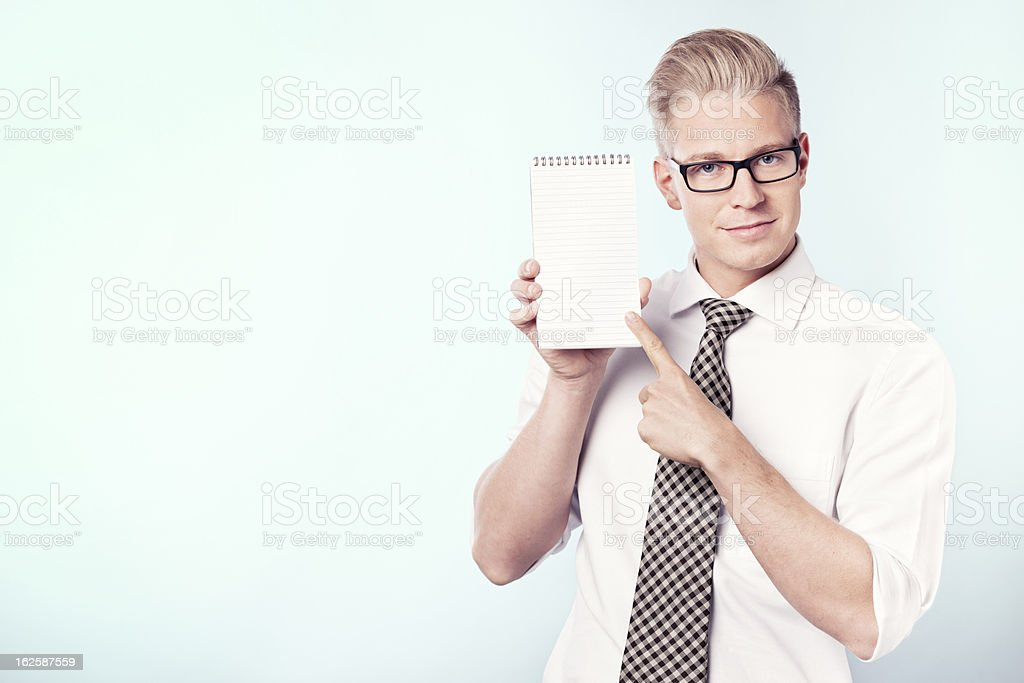 Smiling businessman pointing finger at blank notebook. royalty-free stock photo