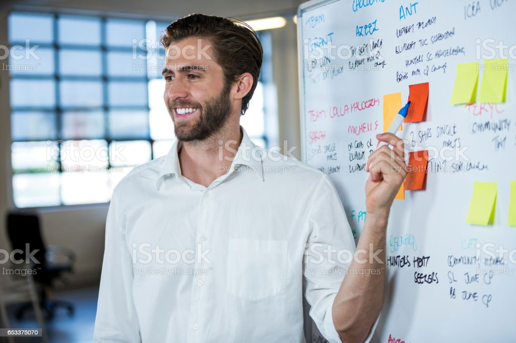 Smiling businessman pointing on sticky note stock photo