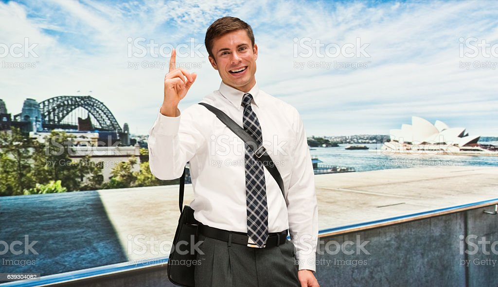Smiling businessman pointing up outdoors stock photo
