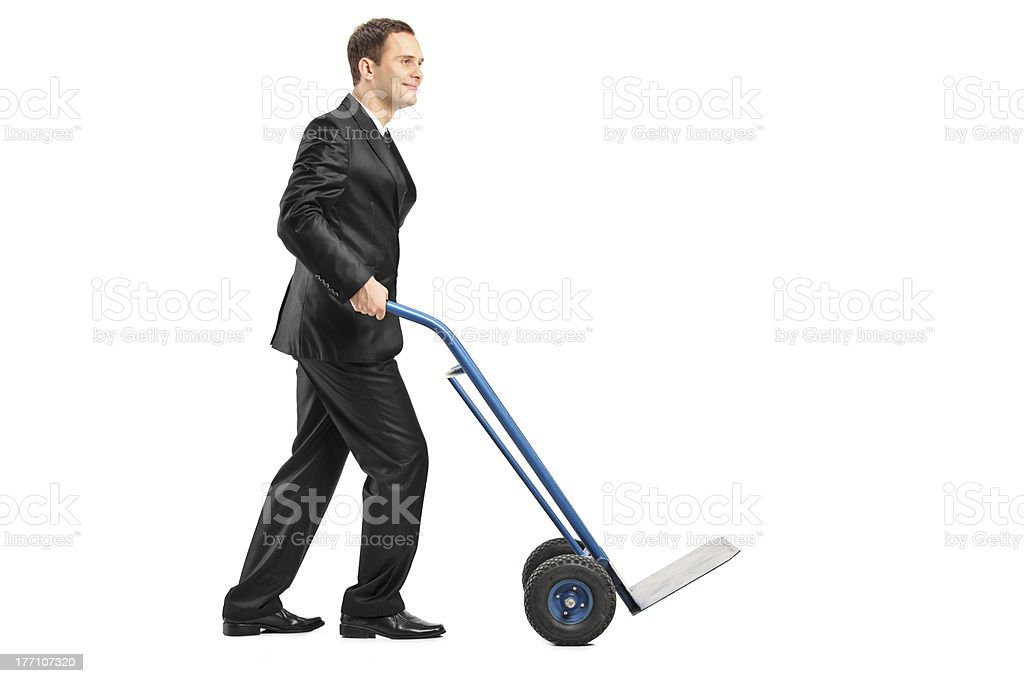 Smiling businessman pushing an empty handtruck stock photo