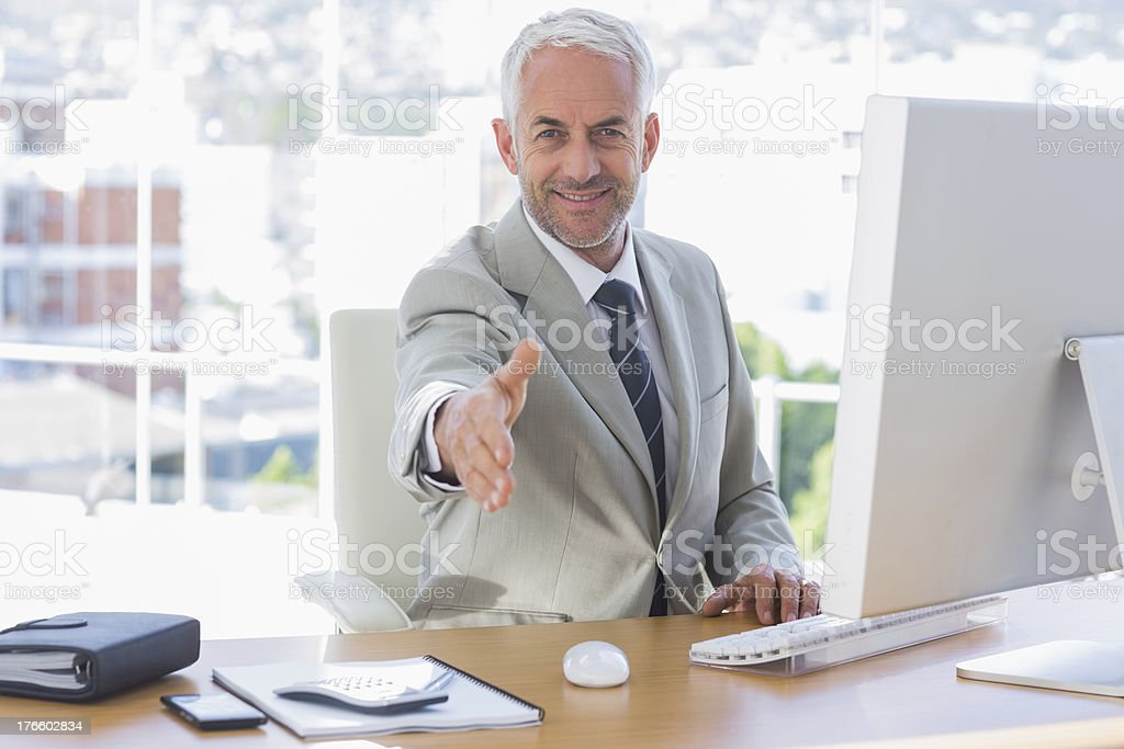 Smiling businessman reaching out arm for handshake royalty-free stock photo