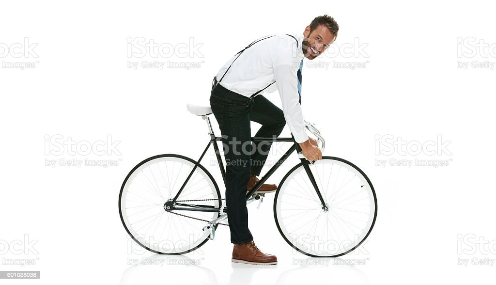 Smiling businessman riding bicycle stock photo