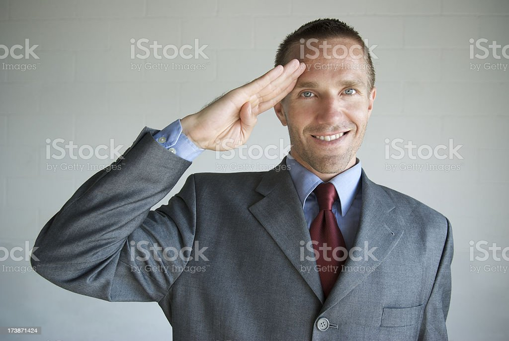 Smiling Businessman Saluting Camera Military Style stock photo