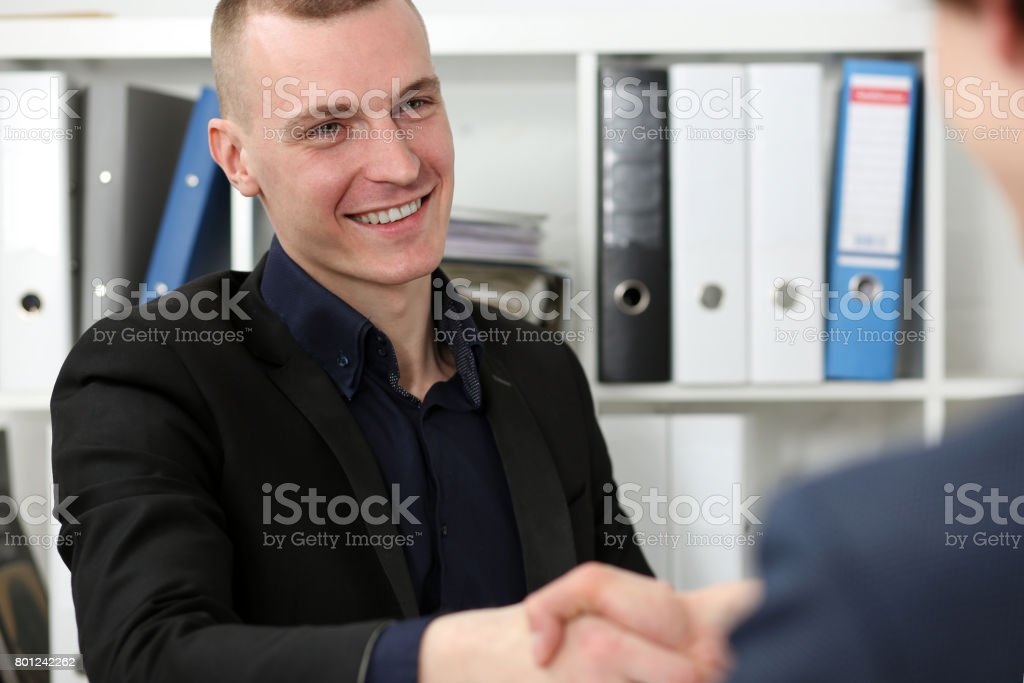 Smiling businessman shake hands as hello in office stock photo