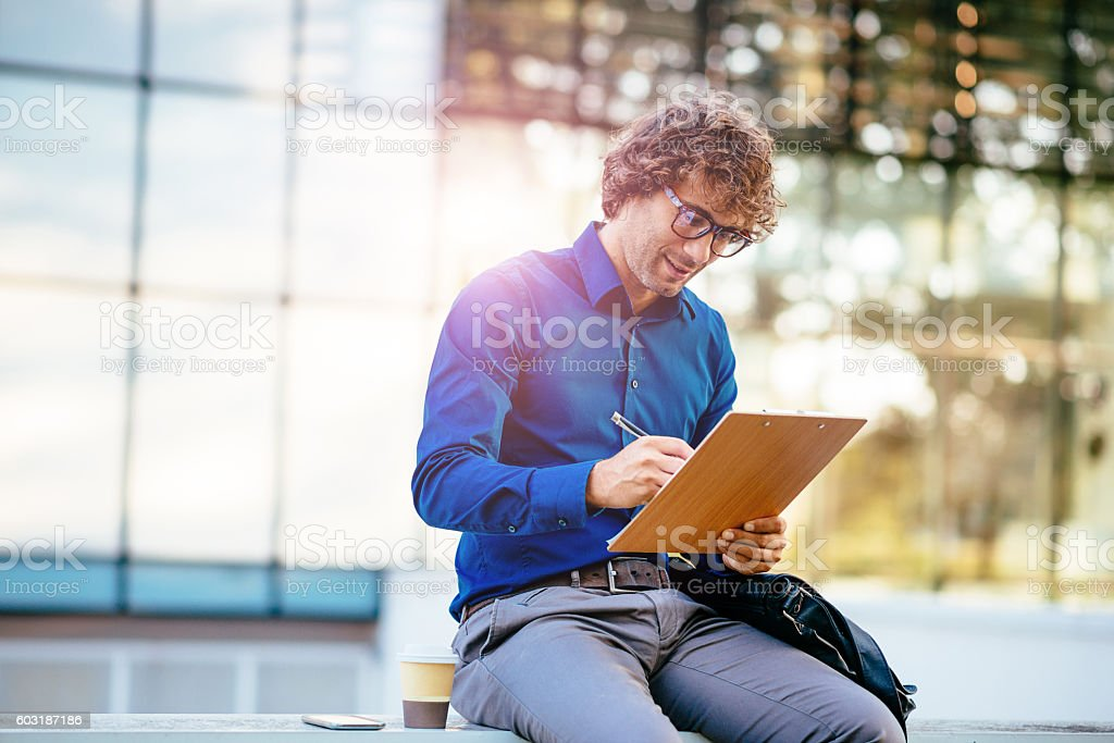 Smiling businessman signing project proposal before sending it stock photo