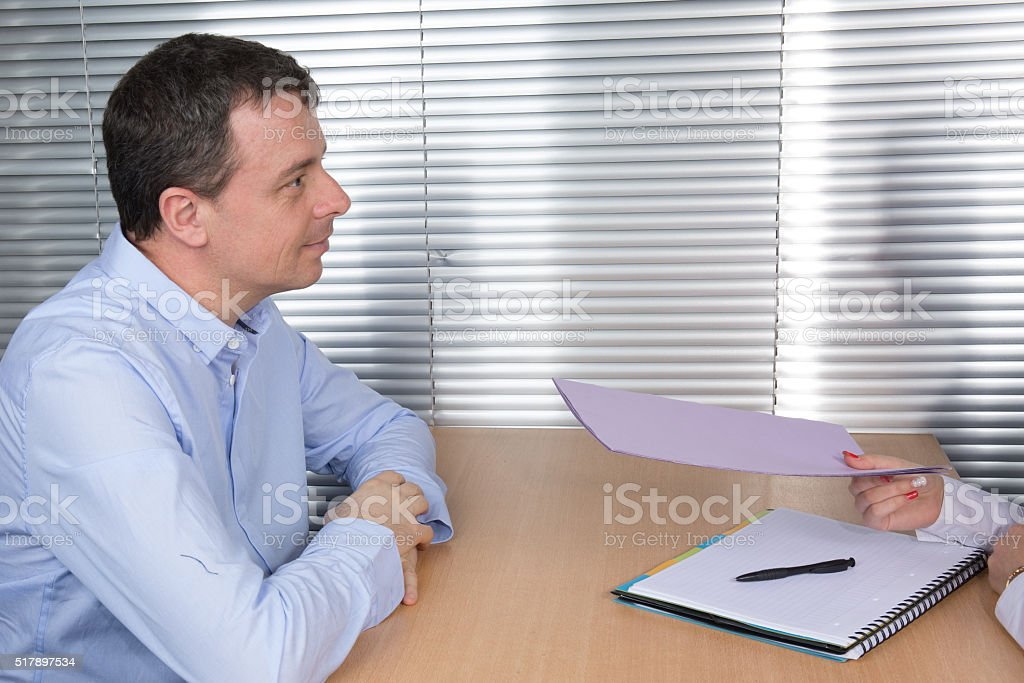 Smiling  businessman sitting at desk receiving a contract from worker stock photo
