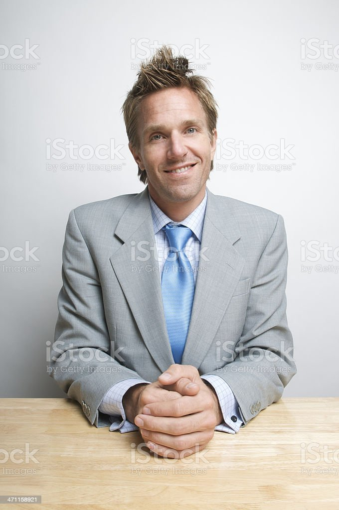 Smiling Businessman Sitting at Desk with Hands Clasped royalty-free stock photo