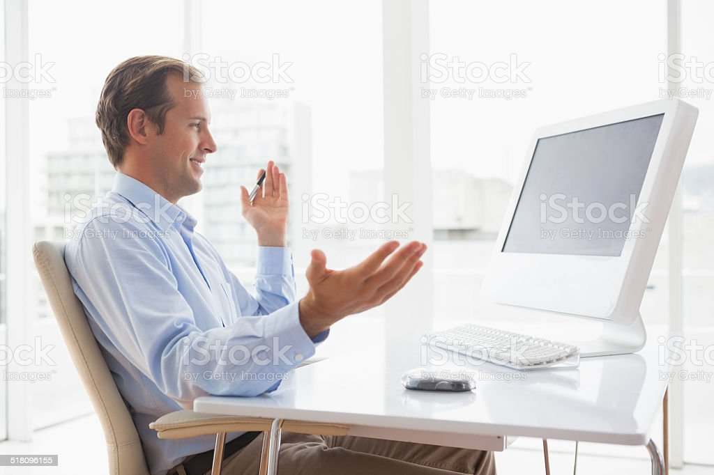 Smiling businessman sitting at his desk on video chat stock photo