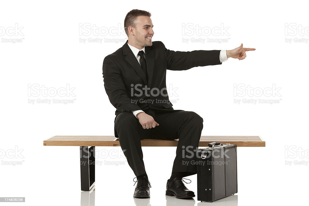 Smiling businessman sitting on a bench and pointing royalty-free stock photo