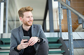 Smiling businessman sitting on staircase holding his mobile phone.