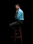 Smiling businessman sitting on stool