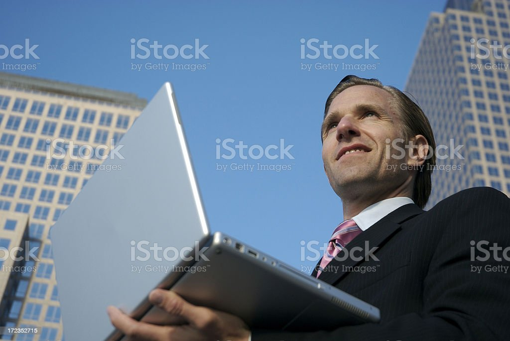 Smiling Businessman Standing City Skyline Outside with Laptop royalty-free stock photo
