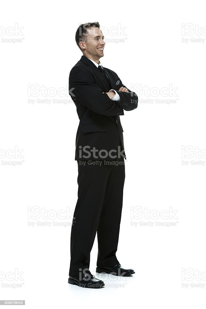 Smiling businessman standing & looking away royalty-free stock photo