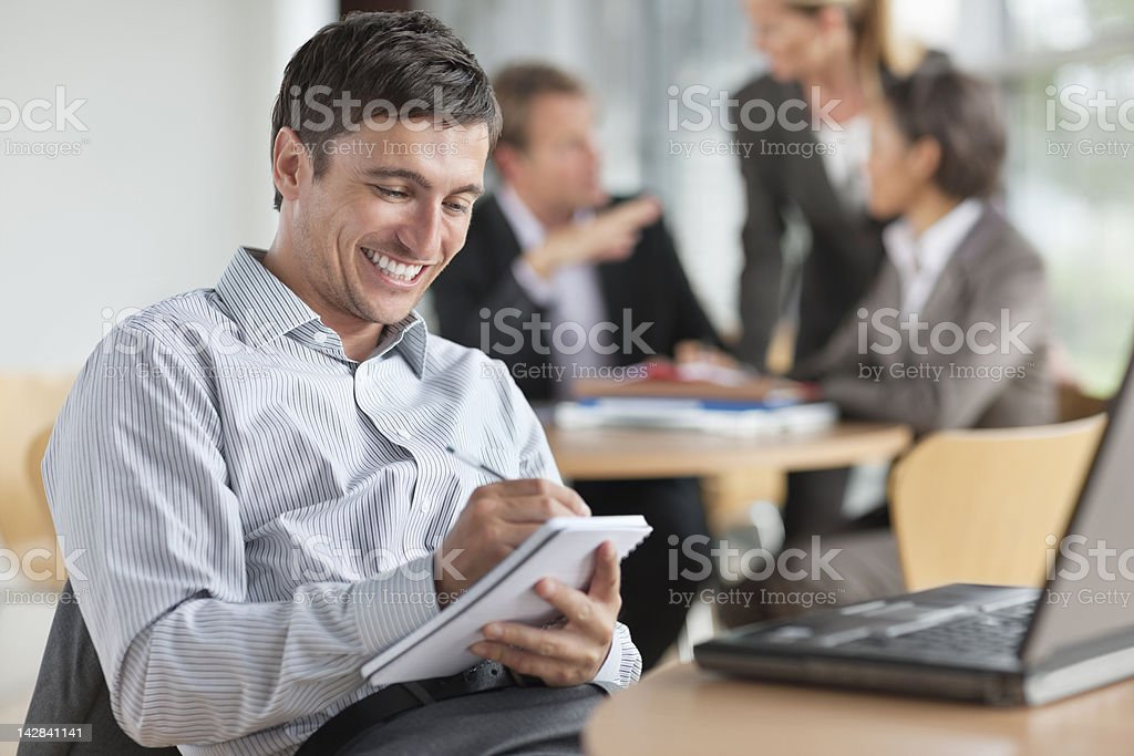Smiling businessman taking notes at table royalty-free stock photo