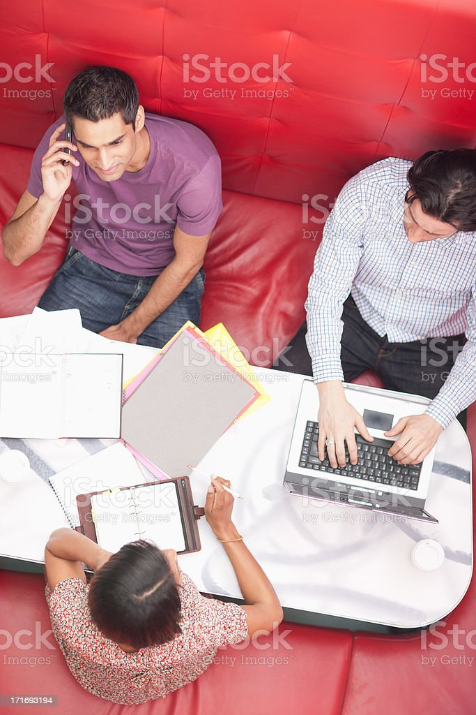 Smiling businessman talking on cell phone in meeting royalty-free stock photo