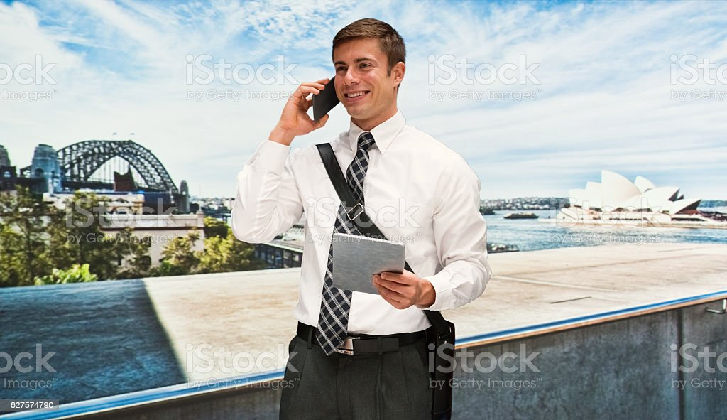 Smiling businessman talking on phone outdoors stock photo