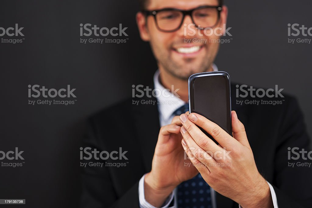 Smiling businessman text messaging on smart phone royalty-free stock photo