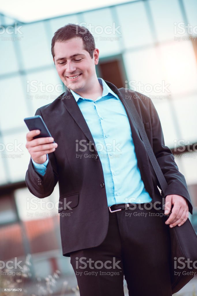 Smiling Businessman Texting On The Mobile Phone In Front of Office Building stock photo