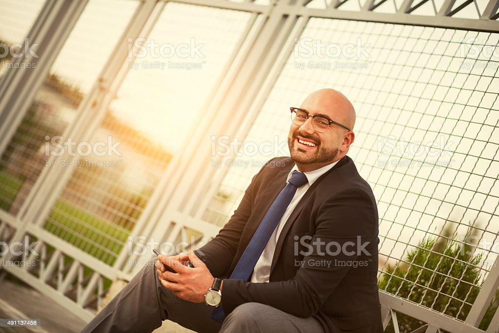 Smiling Businessman using a Smartphone on Break from Work stock photo