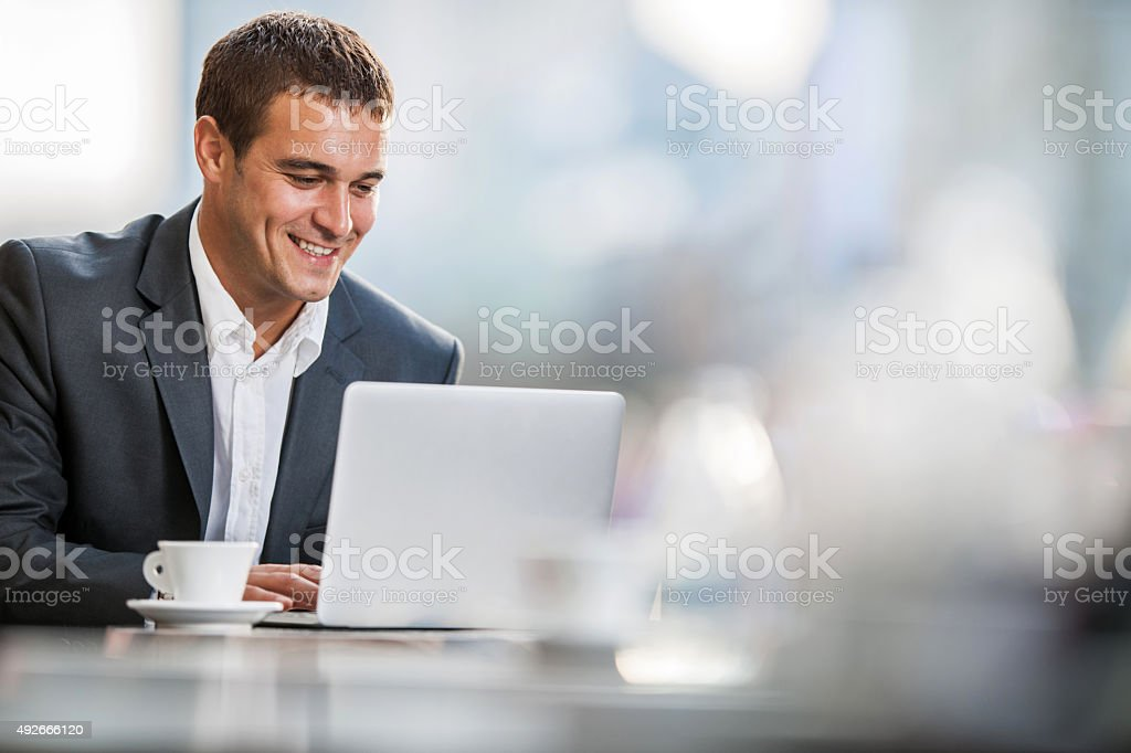Smiling businessman using computer on a break in a cafe. stock photo