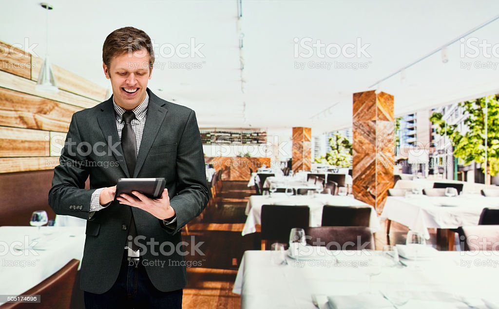 Smiling businessman using tablet in restaurant stock photo