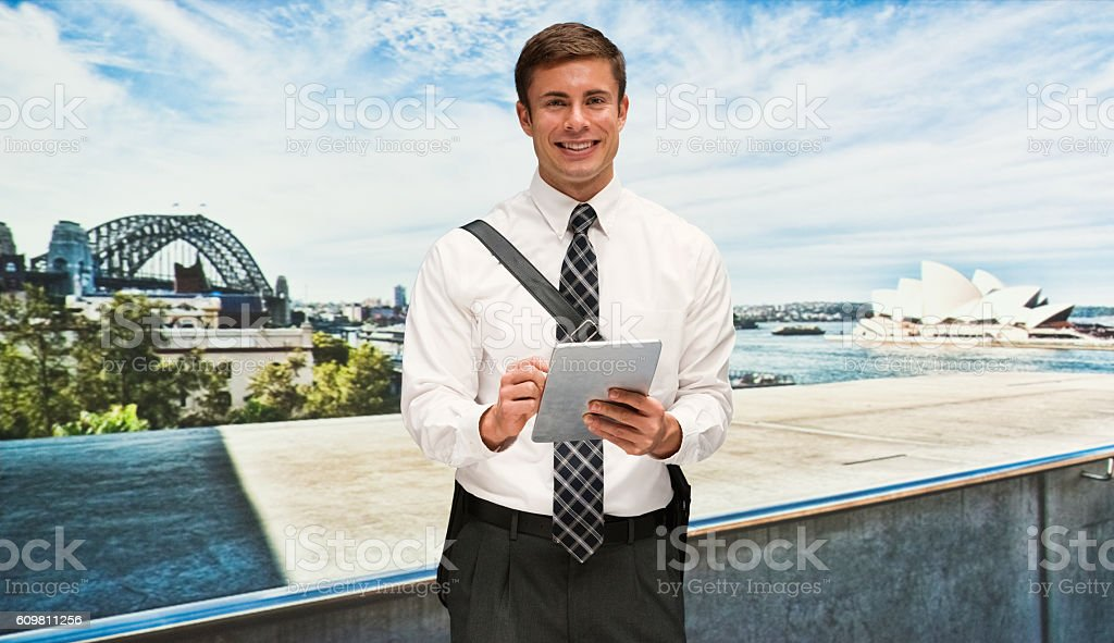 Smiling businessman using tablet outdoors stock photo