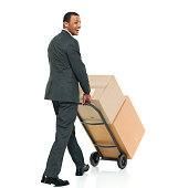Smiling businessman walking with hand truck
