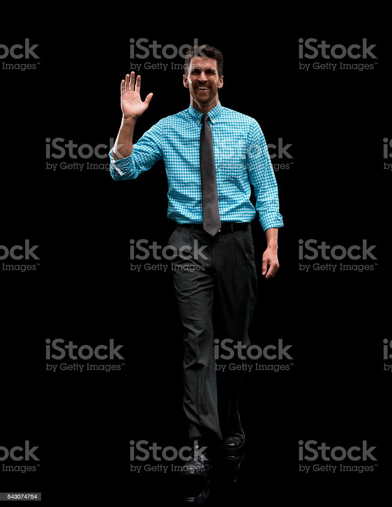 Smiling businessman waving hand and walking stock photo