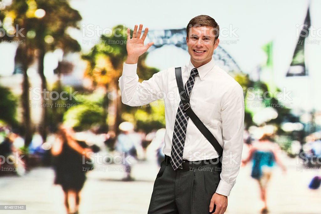 Smiling businessman waving hand outdoors stock photo