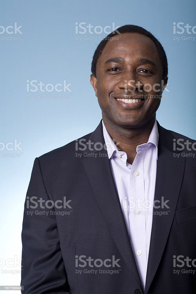 Smiling businessman with blue background stock photo