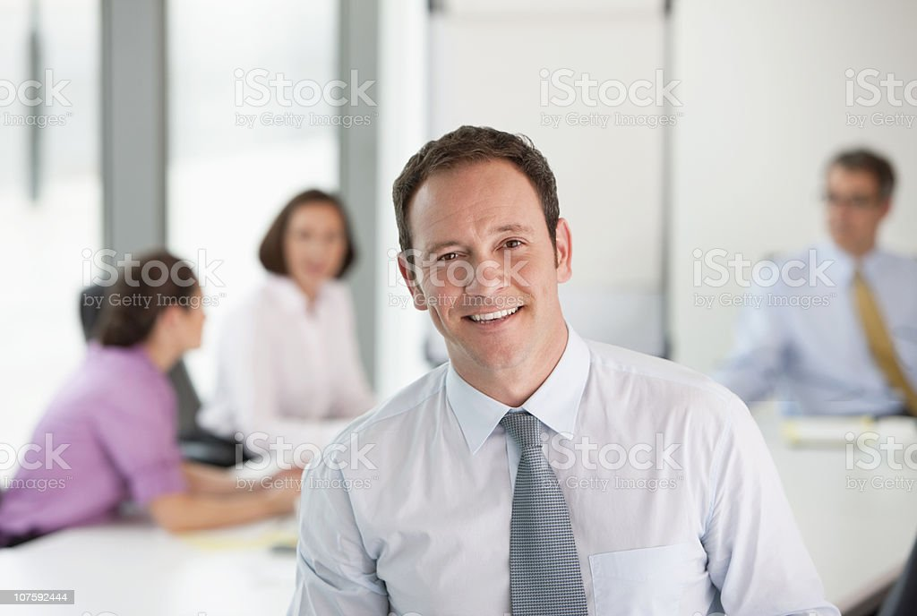 Smiling businessman with colleagues in background at conference room royalty-free stock photo