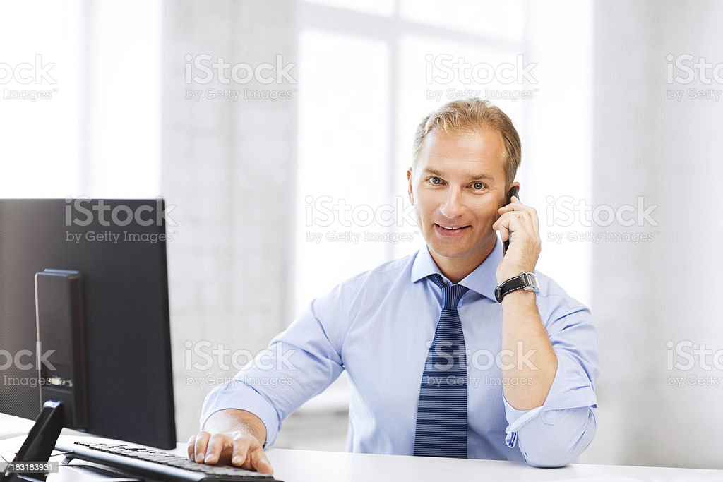 smiling businessman with computer calling on smartphone in office royalty-free stock photo