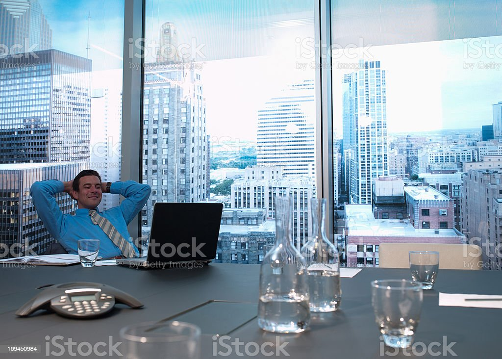 Smiling businessman with hands behind head in conference room royalty-free stock photo