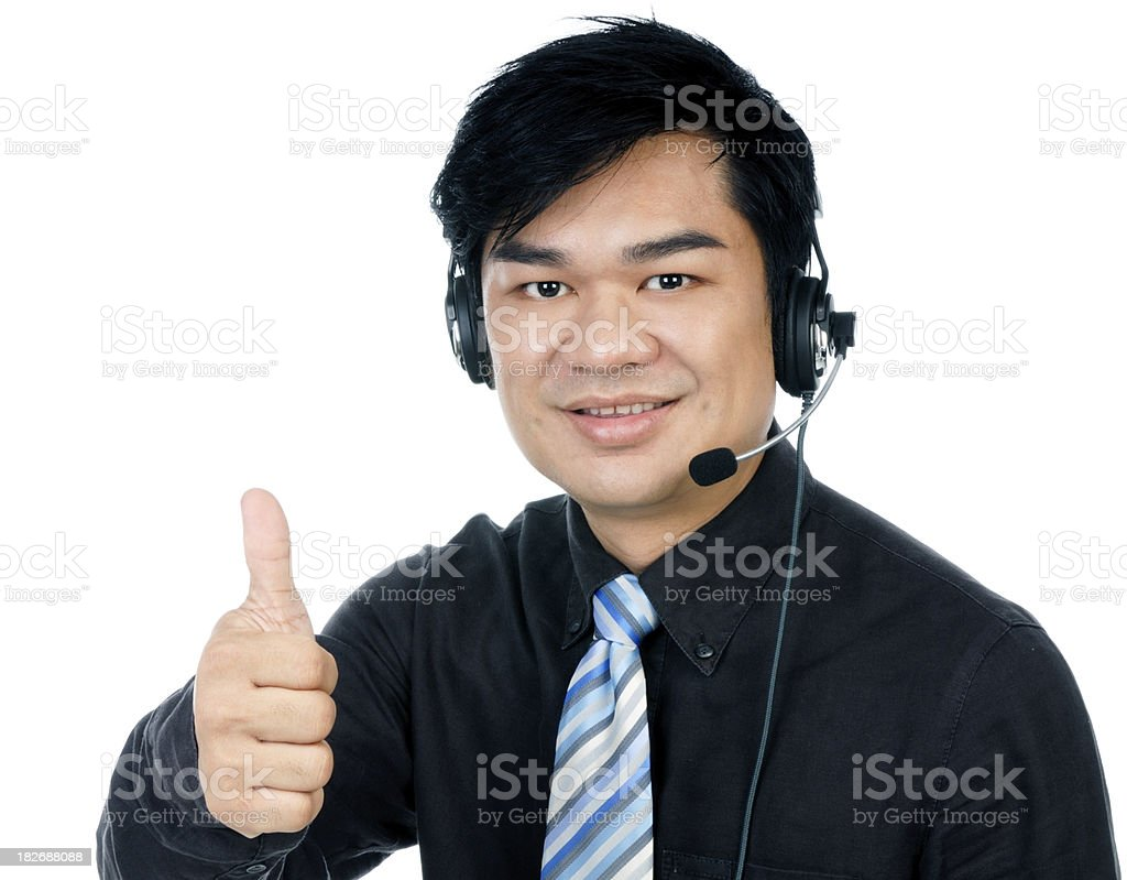 Smiling businessman with headset giving thumbs up  sign royalty-free stock photo